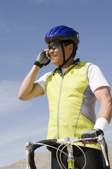 Senior man with bike talking on cell phone