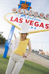 Young woman wearing hat in front of Welcome to Las Vegas sign