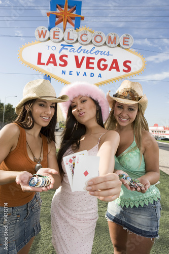Women holding cards and gambling chips in front of Las Vegas welcome sign, Nevada, USA