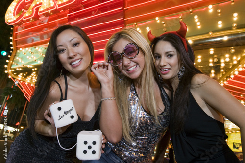 Portrait of three young women with fuzzy dice in front of illuminated casino, Las Vegas, Nevada, USA