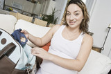 Pregnant woman packing baby clothes