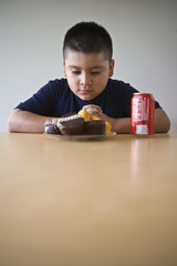 Pre-teen 10-12 boy sitting at desk and looking at dessert