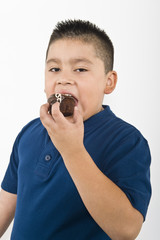 Pre-teen 10-12 boy eating cookie