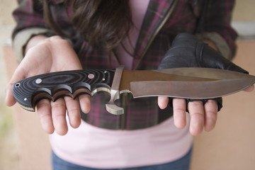 Young woman holding knife on her palms