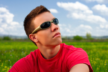 Teenager with sunglasses and red shirt looking up.