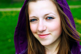 Young teenage girl smiling with mauve hood.