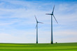 canvas print picture Wind turbines farm in green field over cloudy sky