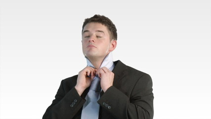 Young businessman putting a tie on