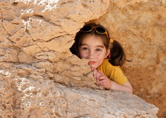 Cute little girl hides behind a rock