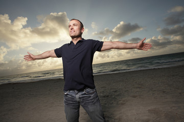 Man with arms outstretched at the beach