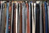 A rack of mens pants in a second hand shop