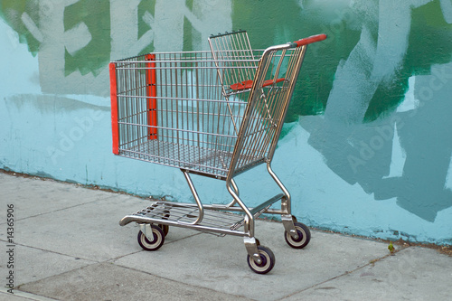 Urban scene with a shopping cart parked by a painted alley wall