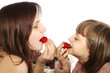 two little girls eating a strawberries