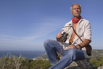 Model explorer posing outdoors with is binoculars