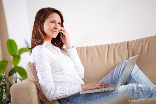Frau mit Laptop beim telefonieren
