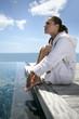 Jeune femme en peignoir assise au bord d'une piscine