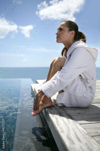 Jeune femme en peignoir assise au bord d 39 une piscine for Peignoir piscine