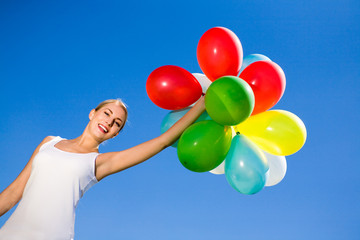Woman holding balloons against blue sky