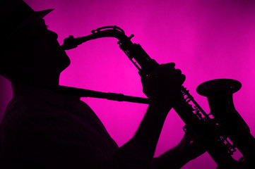 Saxophone Played in Silhouette Pink Background
