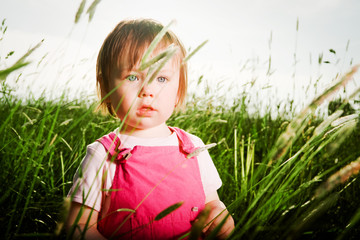 Baby girl in tall grass