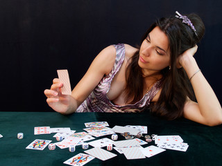 Gambling woman in hesitation holding one card