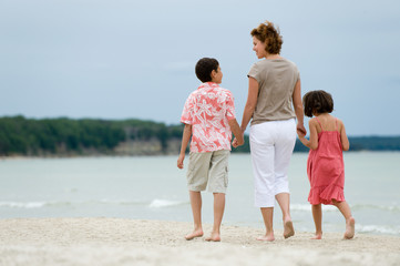 Mother and kids walking on the beach