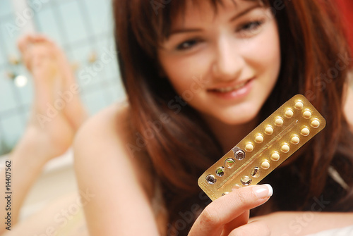 Happy girl looking at her contraceptive pills