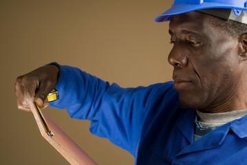Construction Worker Measuring Tile