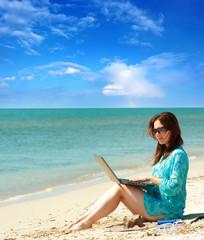 girl using a laptop near the sea