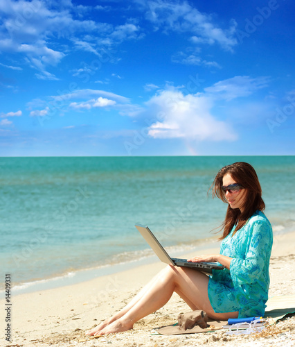girl using a laptop near the sea