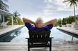 Homme âgé assis sur une chaise au bord d'une piscine
