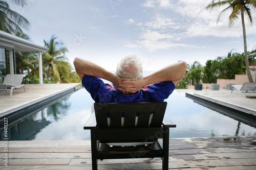 Homme âgé assis sur une chaise au bord d'une piscine - 14411327