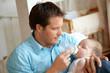 Leinwandbild Motiv Mann der Baby fŸttert