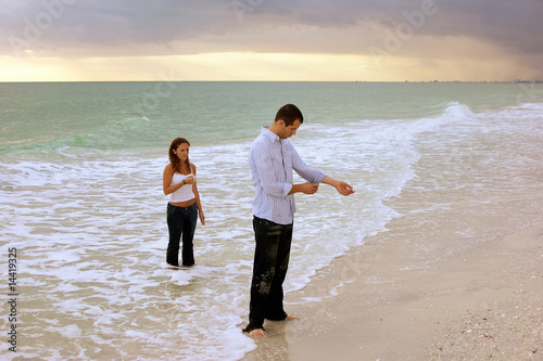 fully clothed couple standing in ocean at sunset