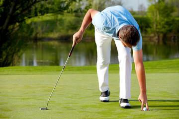 Golfer nimmt den Ball aus dem hole