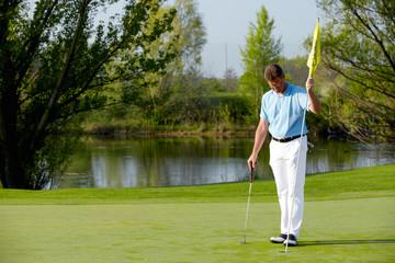 Golfer bedient Flaggstock