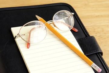 Eyeglasses, pencil and notepad