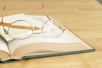 Eyeglasses with pencil and yellow notepad on open book