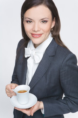 The woman in a business suit holds a cup with tea
