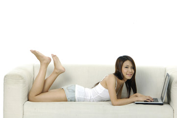 Beautiful woman working lying on the sofa with her laptop