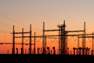 Silhouetted power pylons against a red sky at sunset
