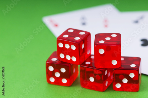 Red dice and cards at the green background