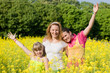 Mother and two daughter fun on meadow full of yellow flowers. So