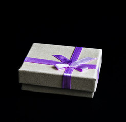 Silver box with violet bow isolated from black