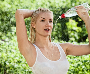 Sexy young woman drinking water under rain