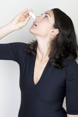 Young woman using nose drops isolated on white background
