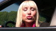 young woman gives a kiss / puckered lips out oft the car
