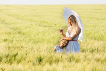 loving mother and daughter under white umbrella in green field