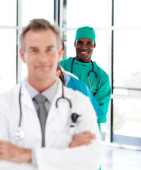Smiling surgeon with folded arms in a line
