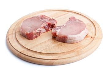 raw pork chops on chopping board